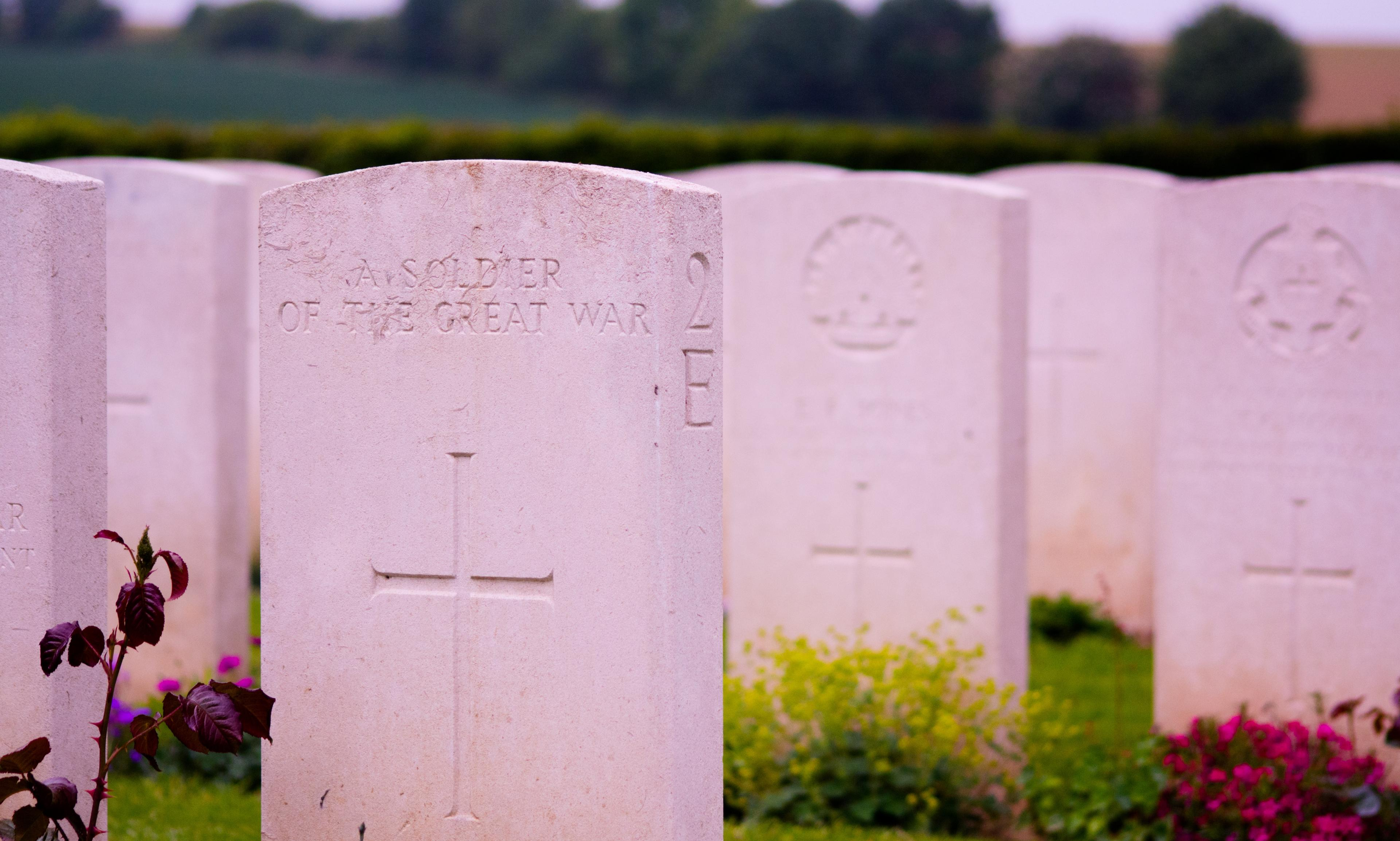 A row of white military gravestones; the closest one is engraved with a cross and the inscription