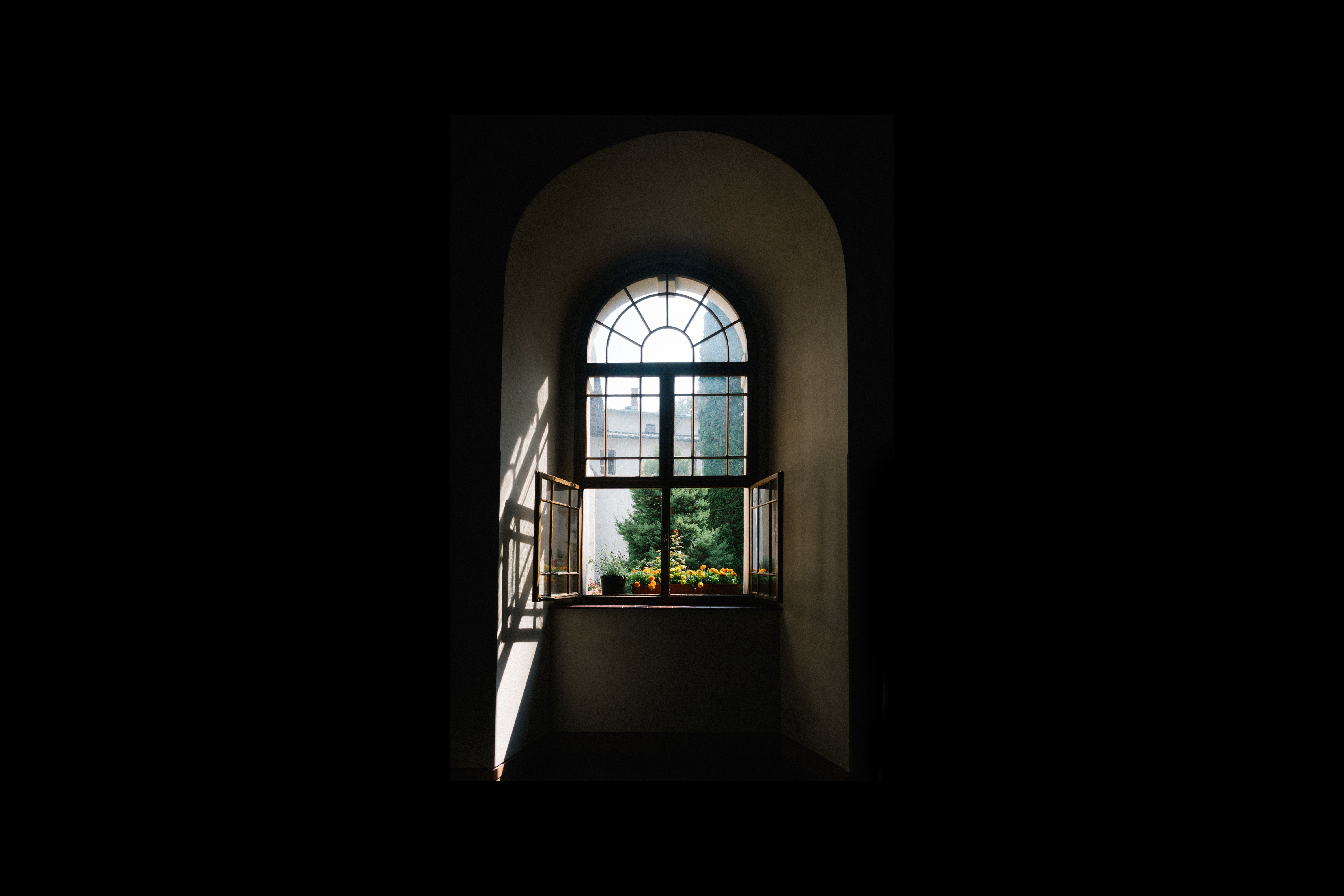 Sunlight streams through a rounded window.