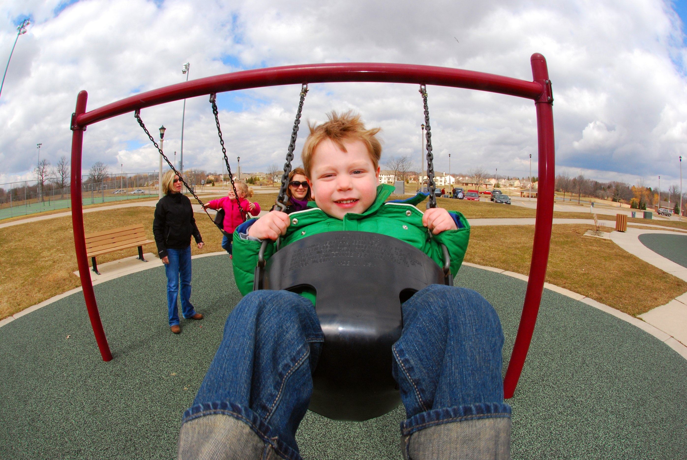 A close-up of a young, smiling child swinging on a playground swing