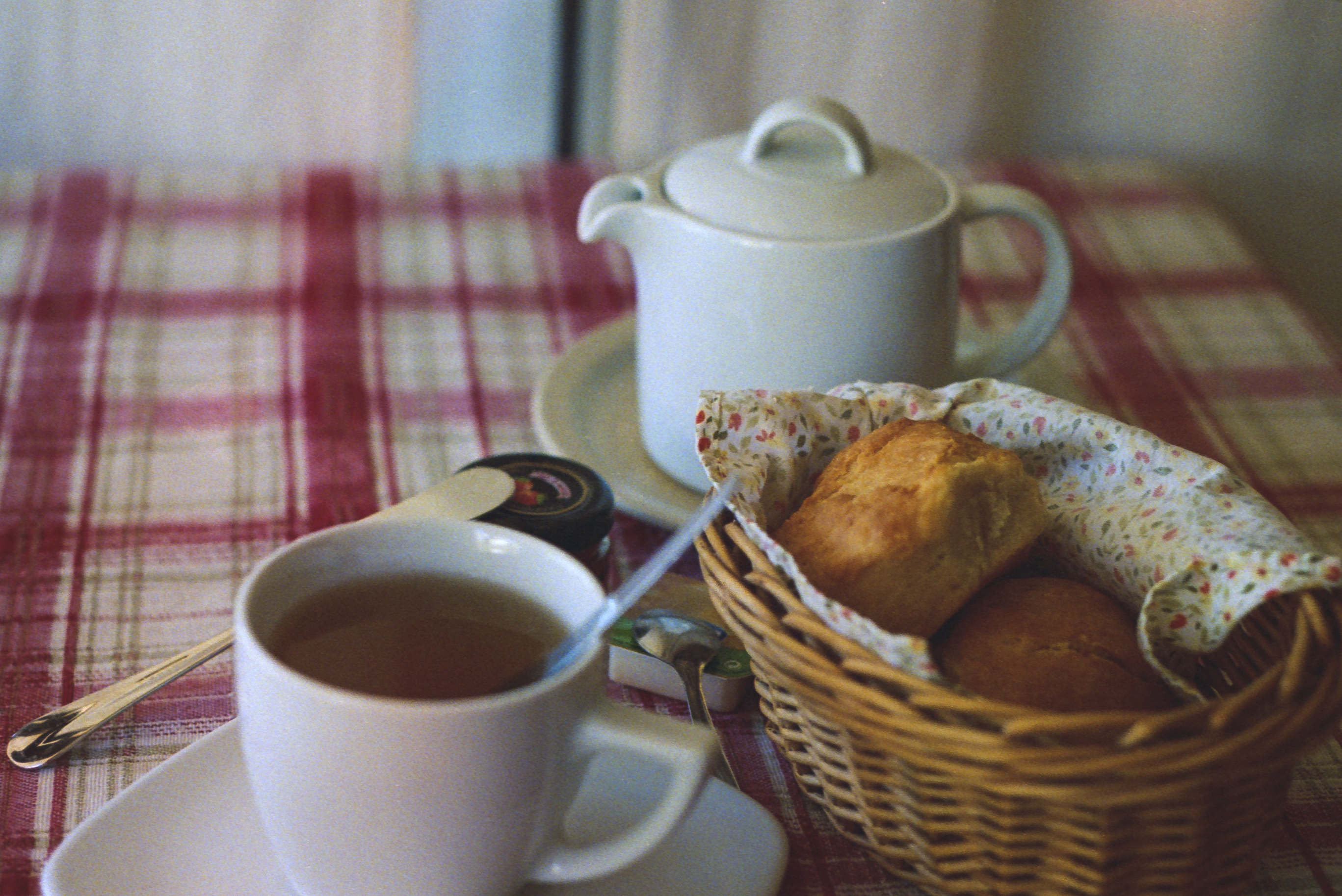 Teapot and cup of tea next to muffins