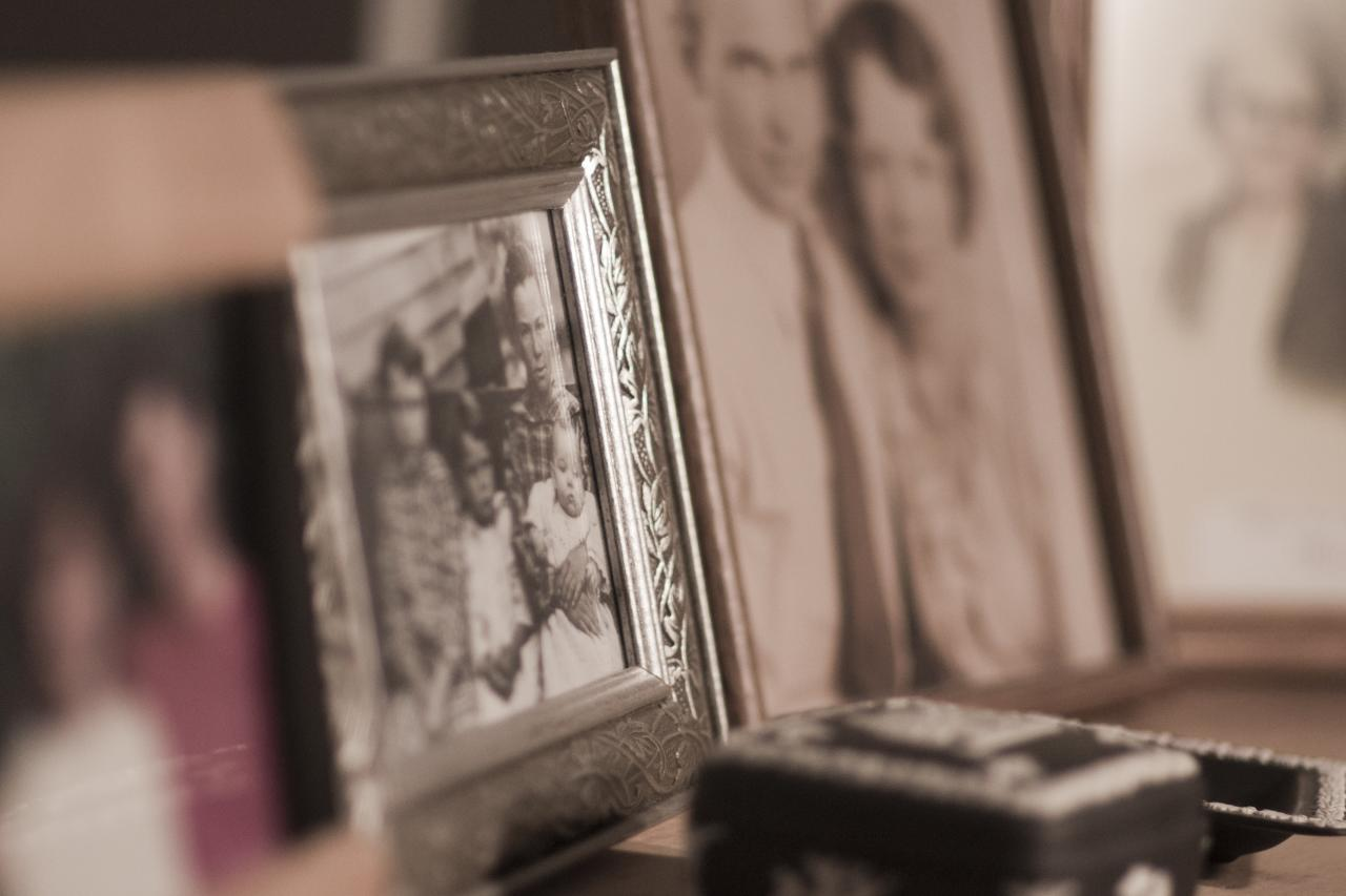 A close-up of framed photographs. In the foreground, a blurry color photo of two people. In the background, vintage-looking black-and-white photos of couples.