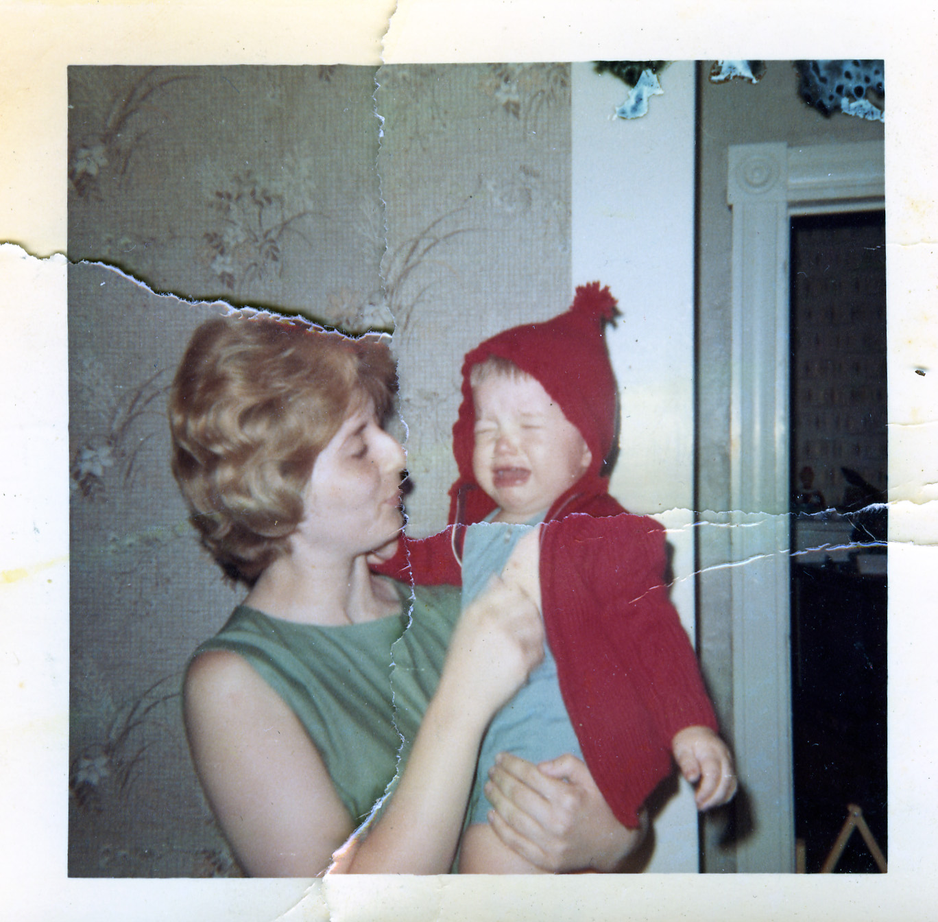 In an old photo that's been torn and taped back together, a mom holds and comforts a wailing child