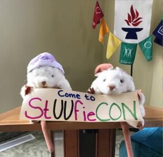 "Two stuffed mice sitting on a lecturn holding a sign saying ""Come to StUUfieCON"""
