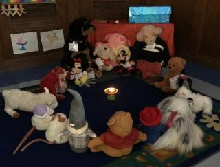 Stuffed animals in a circle around a flaming chalice in a darkened room.