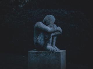 "A sculpture by Jane Mortimer (""Loss""), showing a seated figure with their head tucked against their knees"