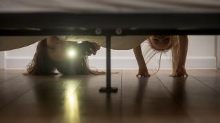 From beneath a bed, a parent and child hang over, flashlight pointed at the camera, as if checking for monsters under the bed.