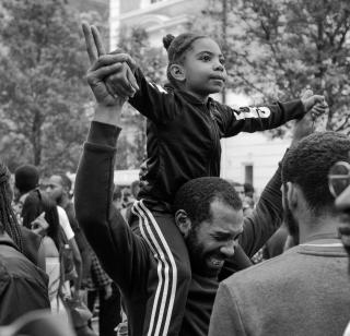 A small black child rides on their father's shoulders, as the two hold hands