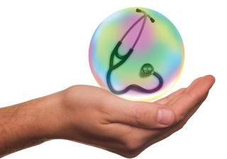 stethoscope in colorful orb held in person's palm