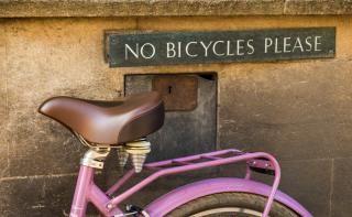 Underneath a plaque, affixed to a wall, that says NO BICYCLES PLEASE, a bicycle is leaning on the wall.