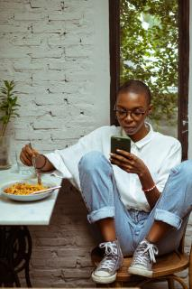 Black person sitting in a chair, reading cell phone while eating a plate of spaghetti