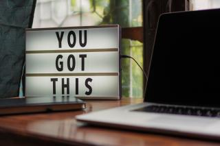 Laptop on a desk with a sign that says You Got This