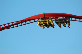 Against a blue sky, a bright red spiral of roller coaster track carries yellow cars of passengers, who are suspended upside down.