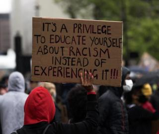 "a black person facing away from camera holding a sign which reads, ""It is a privilege to educate yourself about racism rather than experiencing it!"""