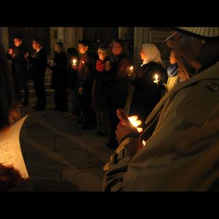 People bundled up against cold weather, standing outdoors in a circle with lit candles in a vigil.