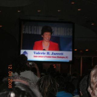 A room full of people watch a screen showing Valerie B. Jarrett addressing the crowd.