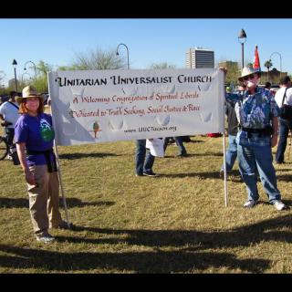 Members of the Unitarian Universalist Church of Tuscon hold a banner at a rally, declaring themselves to be 'A Welcoming Congregation of Spiritual Liberals Dedicated to Truth Seeking, Social Justice & Peace.'
