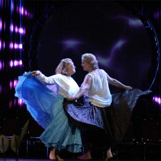 Two women in a stylized dance, their skirts flaring as they face each other in front of an elaborately lit stage.
