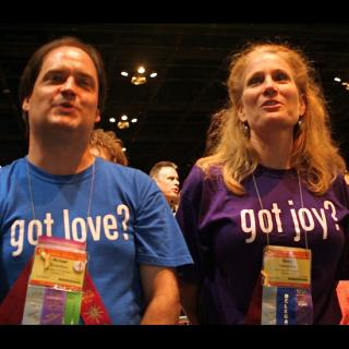 Two UUs enjoy the GA Opening Ceremony; one is wearing a shirt that asks, 'got love?' and the other a shirt that reads, 'got joy?'
