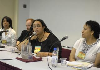 Taquiena Boston, Keith Kron, Sofia Betancourt (speaking), and Paula Cole Jones at sit at the panel's table during a workshop.