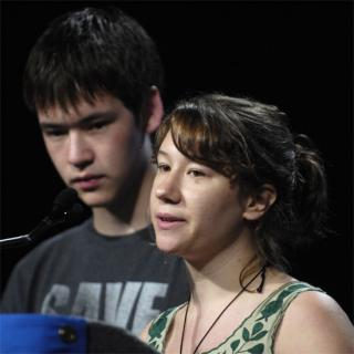 Two youth speaking at a microphone.