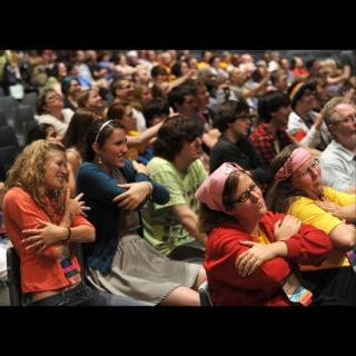 Participants in the New Epiphany Revival hug themselves during a song with movement, led by Nick Page.