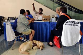 An accessibilities services volunteer directs a General Assembly attendee and their guide dog.