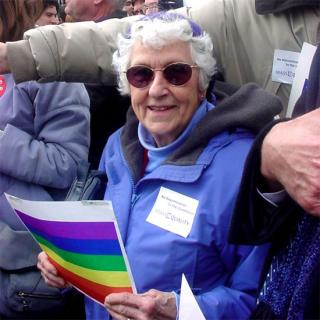 Natalie Gulbrandsen holding a rainbow placard at a same sex marriage rally in 2004.
