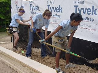 3women_blueshirts_shoveling_dirt_foundation_tyvek_background
