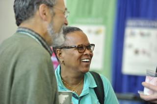 Rev. Cheryl Walker smiles during conversation with two others.