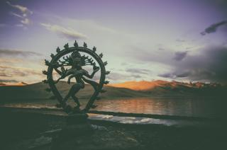 Shiva Nataraja at dusk on the shores of a placid lake, with mountains in the distance.