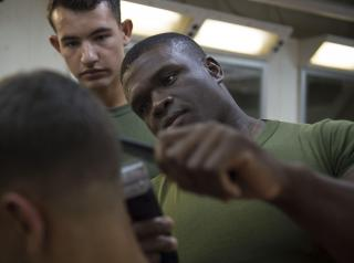 A US naval sargeant cuts a man's hair as another seaman looks on.