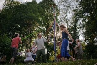 People of many ages dance around a maypole in spring.