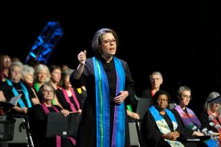 President Susan Frederick-Gray preaching on stage at GA 2018