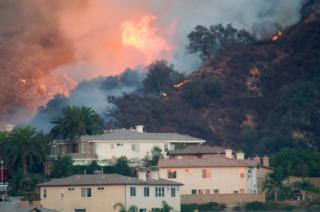 Wildfire overtakes homes in California hills