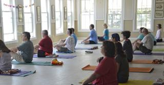 people on yoga mats in a seated pose in a large room with many windows