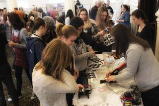 Participants making buttons at a station in the Action Fair during the 2017 UU-UNO Intergenerational Spring Seminar