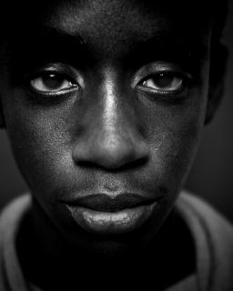 a young African American man gazes into the lens in this piercing portrait