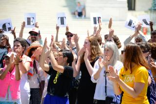 A crowd of Unitarian Universalists cheers in front of the US Supreme Court.