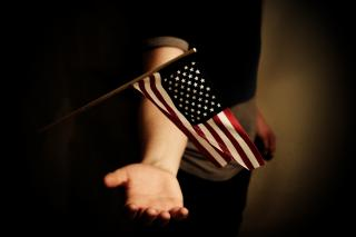 A child's hand extends beneath a small U.S. flag