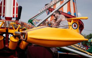 "A father and child, laughing, ride a brightly colored ""rocket"" car on a carnival ride."