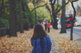 On a city street strewn with fallen leaves, a person with long hair is seen from behind, wearing a backpack.