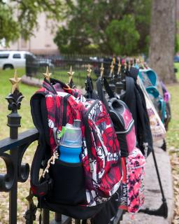 A range of schoolchildren's backpacks are hung on a wrought-iron fence
