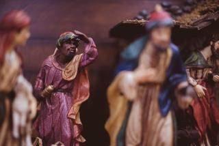 The magi figure from a nativity set, with his hand held above his eyes as though searching. Other magi figurines are blurred in the foreground.