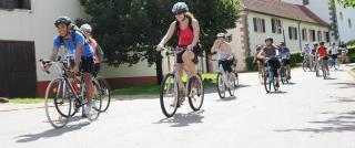 On a sunny street, a dozen helmeted bicyclists ride with smiles on their face