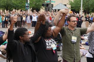 Black Lives Matter activists, including the Rev. Osagyefo Sekou, Amanda Weatherspoon, and Chris Crass, lead an unauthorized rally and die-in that blocked an intersection near the UUA General Assembly convention center June 28. (© Christopher L. Walton)