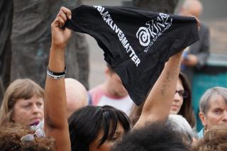 "A Black woman raises a black bandana which reads ""Black Lives Matter"" in a crowd of people"