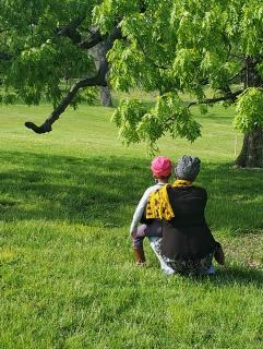 A Black daughter sits on her mother's knee in a grassy park under a tree