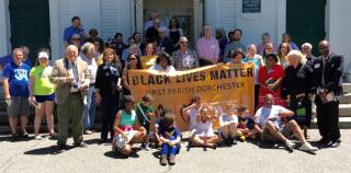 Dorchester UU congregation assembled in front of church with their new Black Lives Matter banner