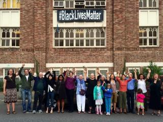 "People stand below a banner displaying the phrase ""Black Lives Matter"""