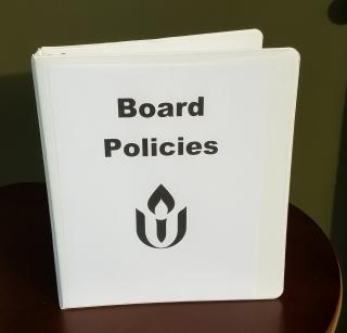 A binder marked board policies with a UUA chalice